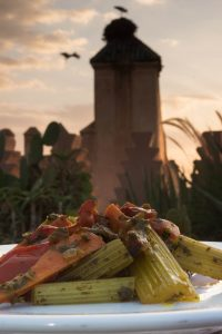 Meat tagine being served on the roof terrace of Dar Les Cigognes, with the storks nests atop the Royal Palace opposite